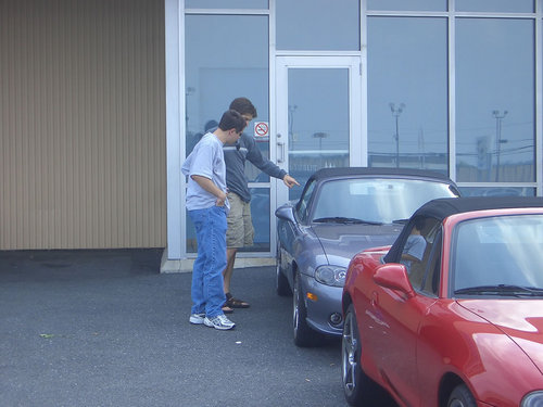 Thad and Owen look at a car